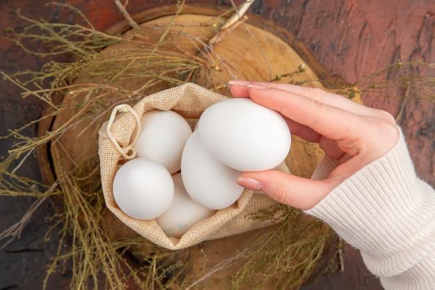 Вид сверху куриные яйца в маленькой сумочке с женской рукой