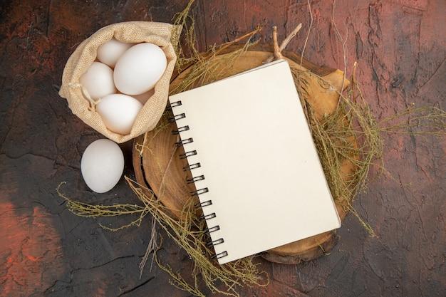 Vista dall'alto uova di gallina all'interno di una piccola borsa con taccuino