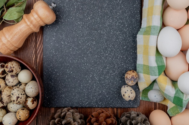 コピースペースを持つ木製の背景に木製のボウルにウズラの卵とチェックのテーブルクロスのバケツに平面図鶏の卵