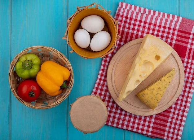 Vista dall'alto di uova di gallina con peperoni, yogurt al pomodoro in un barattolo e formaggi su un supporto su un asciugamano rosso a scacchi su sfondo turchese