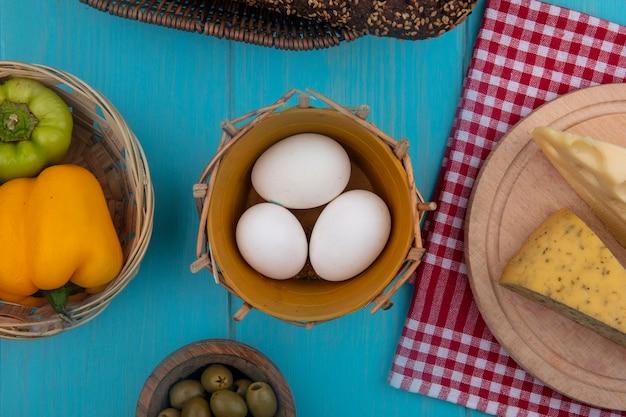 Vista dall'alto di uova di gallina con olive peperoni pomodoro yogurt in un barattolo e formaggi su sfondo turchese