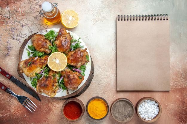 그릇 오일 레몬 크림 노트북에 양파 허브 향신료와 상위 뷰 치킨 포크 나이프 치킨