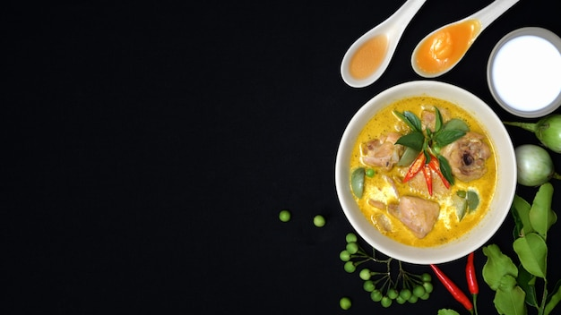 Top view of chicken green curry and ingredients on black desk background, thai cuisine concept