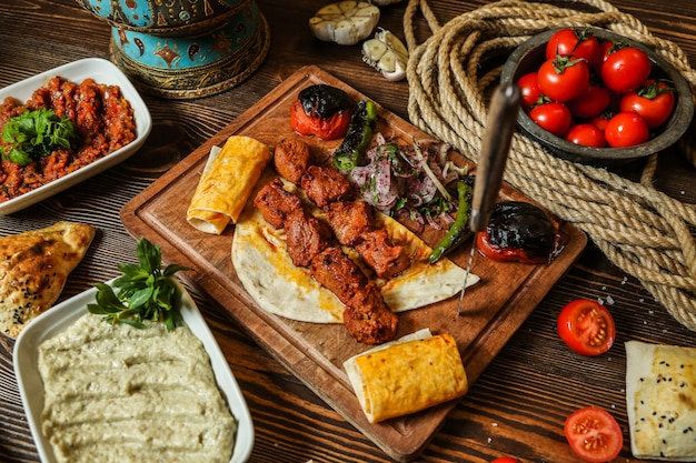 Вид сверху куриный шашлык с жареными помидорами и острым перцем на лаваш на подставке