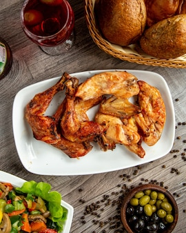 Top view of chicken legs and wings kebab arranged in a plate with a glass of wine on the wooden table