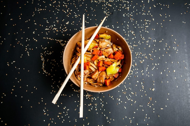 Top view chicken noodles with vegetables in plate with chopsticks and sesame seeds on black background
