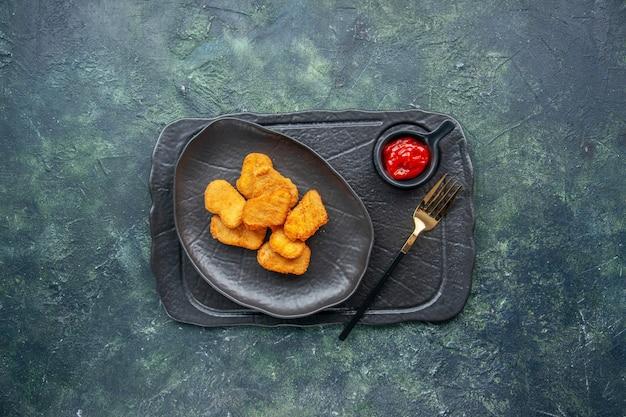 Vista dall'alto di pepite di pollo su un piatto nero e forchetta ketchup su vassoio di colore scuro su superficie scura