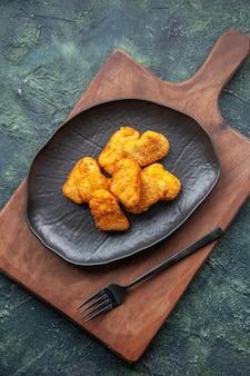 Vista dall'alto di pepite di pollo su un piatto nero e forchetta sul tagliere di legno sulla superficie scura