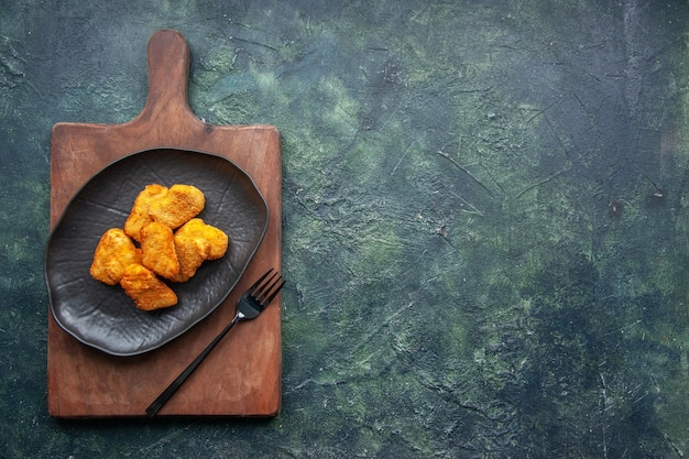 Vista dall'alto di pepite di pollo su un piatto nero e forchetta sul tagliere di legno sul lato destro sulla superficie scura