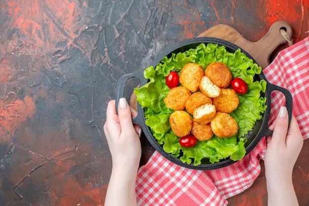 Vista dall'alto pepite di pollo lattuga pomodorini in padella in mani femminili su spazio libero muro rosso scuro