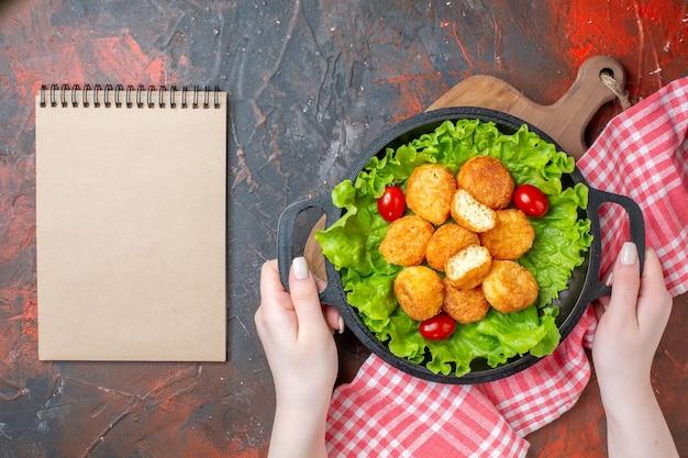 Vista dall'alto pepite di pollo lattuga pomodorini in padella in mani femminili quaderno su muro rosso scuro