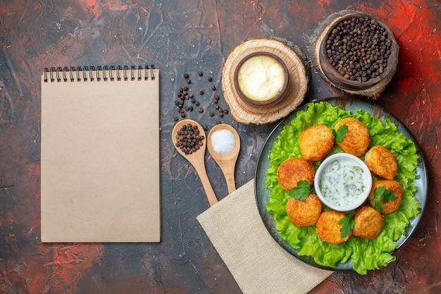어두운 탁자에 있는 나무 그릇 메모장에 있는 접시 소금과 검은 후추에 상위 뷰 치킨 너겟 양상추