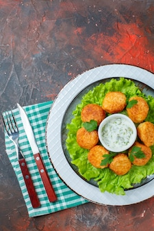 Pepite di pollo vista dall'alto lattuga e salsa sul piatto su spazio libero tavolo scuro