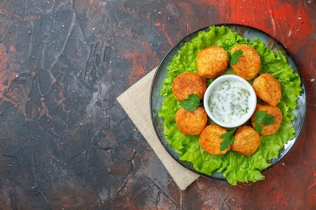Pepite di pollo vista dall'alto lattuga e salsa sul piatto sul tavolo scuro con posto per la copia