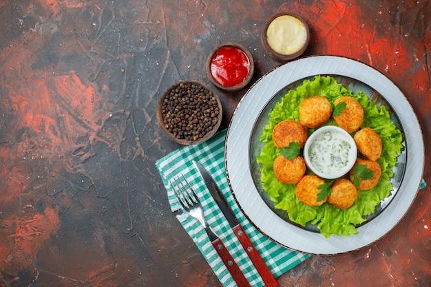 Vista dall'alto pepite di pollo lattuga e salsa su salse al piatto e pepe nero in piccole ciotole coltello e forchetta sul tavolo scuro spazio libero