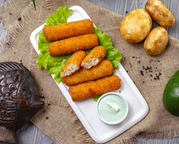 Top view chicken nuggets on lettuce with sauce and unpeeled potatoes