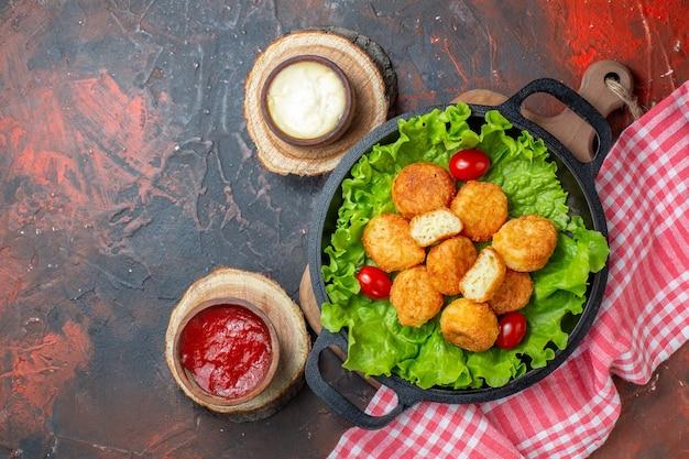 Pepite di pollo vista dall'alto in ciotole di salsa di padella su assi di legno su parete rosso scuro con spazio libero