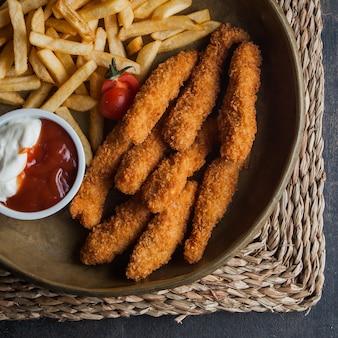 Pepite di pollo vista dall'alto con patatine fritte e sous e pomodoro in piatti di argilla