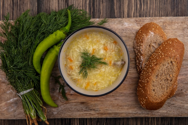 Top view of chicken orzo soup in bowl and seeded brown cob bread slices with dill and pepper on cutting board on wooden background