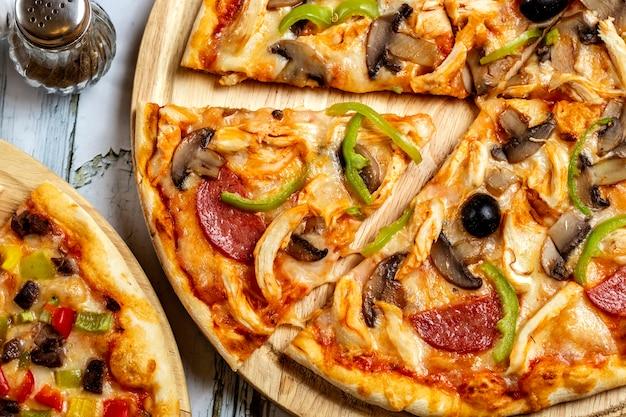 Вид сверху куриная пицца с салями, грибами, болгарским перцем, курицей и черной оливкой