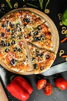 Вид сверху куриная пицца с помидорами, болгарским перцем и оливками на подносе
