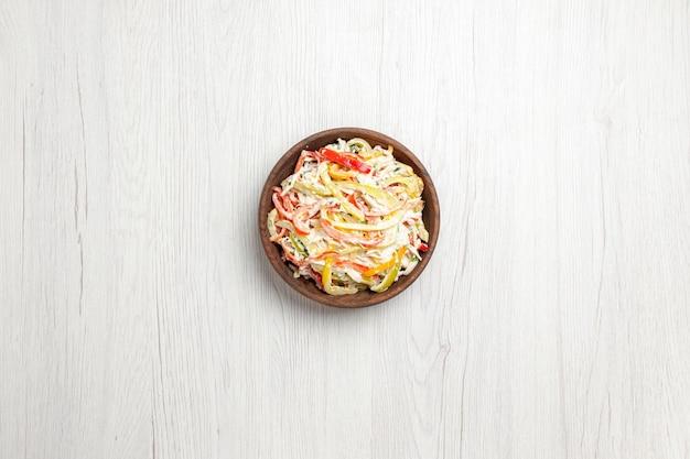 白い机の上のプレートの中にマヨネーズとスライスした野菜を添えたトップビューチキンサラダフレッシュサラダミートスナックミール