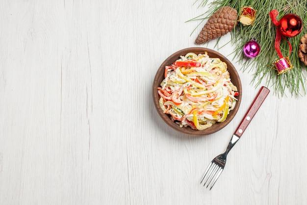 白い机の上のプレートの中にマヨネーズとスライスした野菜を添えたトップビューチキンサラダフレッシュサラダミートミールスナック