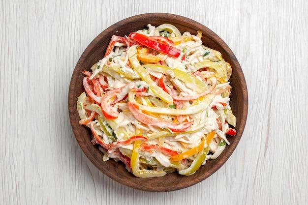 Куриный салат с майонезом и нарезанными овощами внутри тарелки на белом столе, вид сверху, свежий салат, мясная закуска