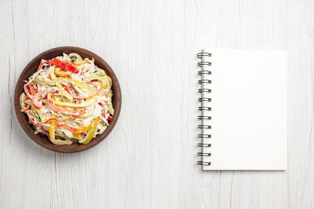 Куриный салат с майонезом и нарезанными овощами внутри тарелки на белом полу, вид сверху, свежий салат, мясная закуска