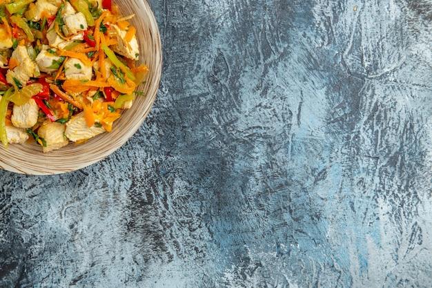 Vista dall'alto di insalata di pollo con verdure su superficie chiara