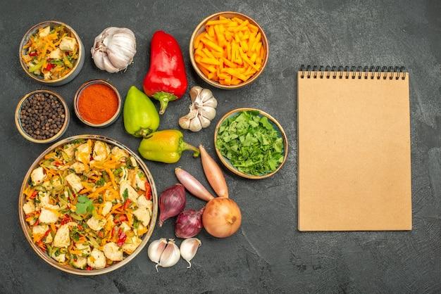 Вид сверху куриный салат с овощами на темном столе диетическое здоровое питание