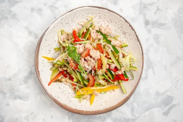 Vista dall'alto di insalata di pollo con verdure su superficie bianca macchiata