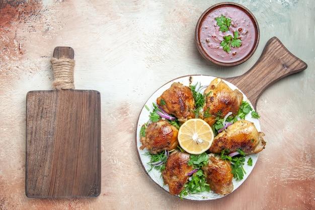Vista dall'alto del pollo in salsa di pollo con cipolla alle erbe su lavash accanto al tagliere