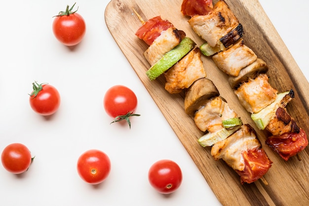 Top view chicken skewers on cutting board with cherry tomatoes