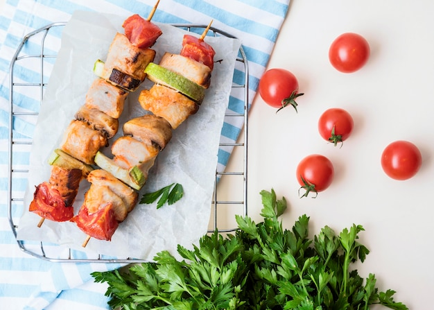 Top view chicken skewers on parchment paper with cherry tomatoes