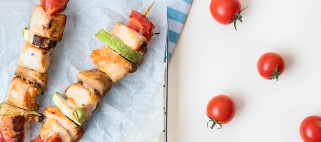 Top view chicken skewers on parchment paper with tomatoes