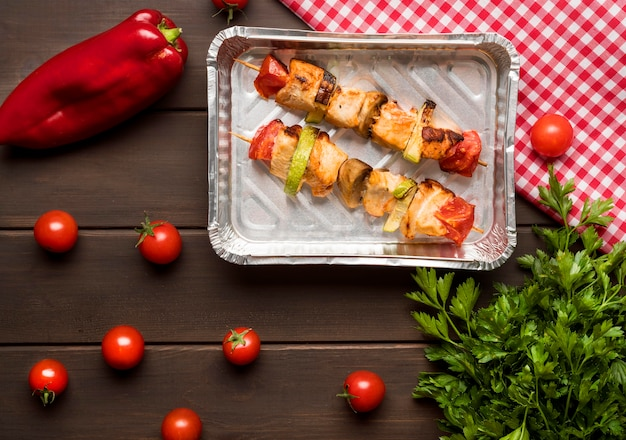 Top view chicken skewers on tray with red pepper and tomatoes