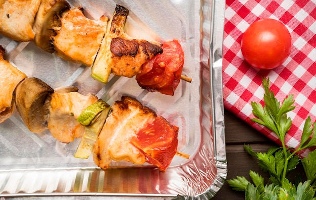 Top view chicken skewers on tray with tomato