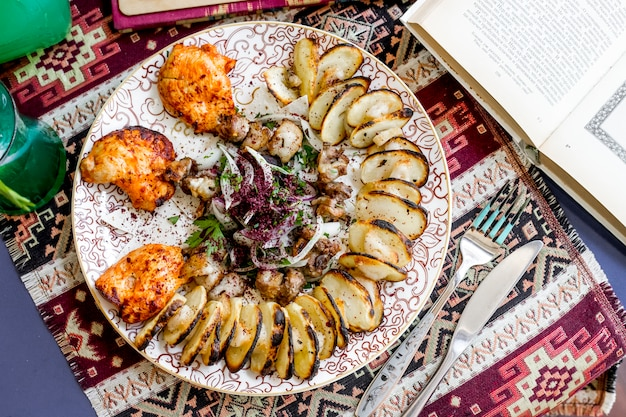 Top view chicken skewers with sliced ‹potatoes onions and herbs sprinkled with sumac