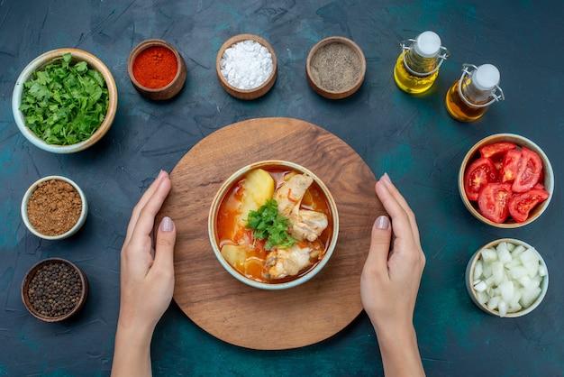 トップビューチキンスープとソルトペッパーオイルグリーン、紺色の表面スープ肉料理ディナーミールの新鮮な野菜
