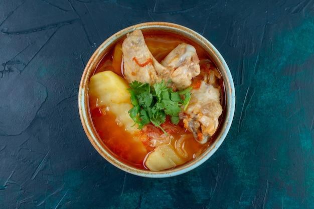 Zuppa di pollo vista dall'alto con pollo e verdure all'interno sul pollo cena cibo carne minestra blu scuro scrivania