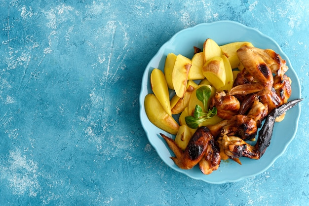 Вид сверху куриные крылышки в маринаде соевого соуса и ломтики печеного картофеля в синей тарелке на синем фоне с копией пространства