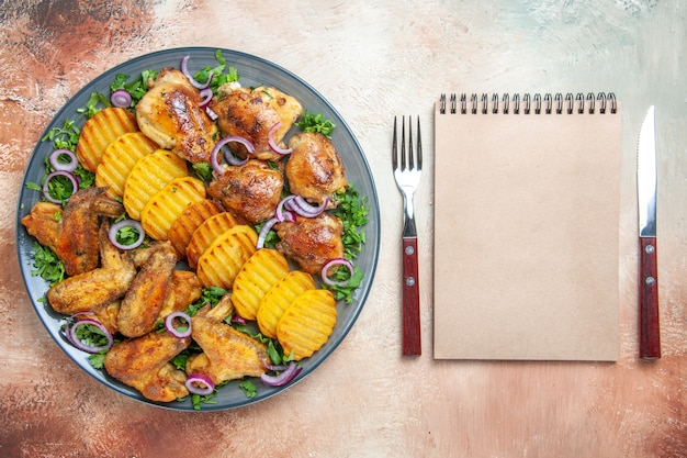 Top view of chicken wings plate of potatoes chicken herbs onions fork knife notebook