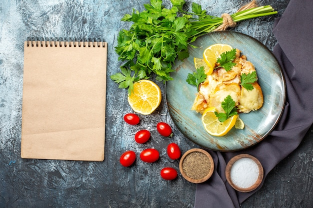 Вид сверху курица с сыром на тарелке, петрушка, лимон, помидоры, черри, блокнот на сером столе