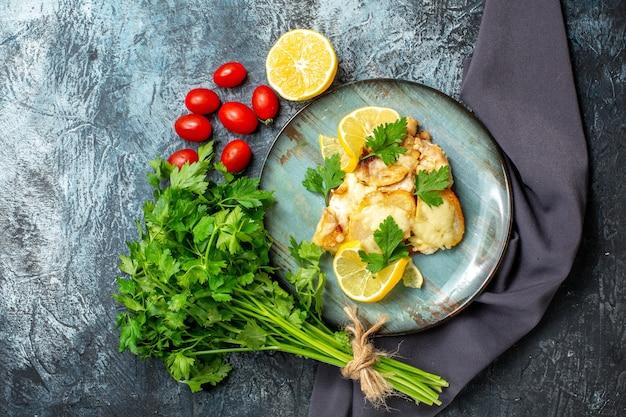 Vista dall'alto pollo con formaggio sul piatto mazzo di prezzemolo mezzo limone pomodorini sul tavolo grigio