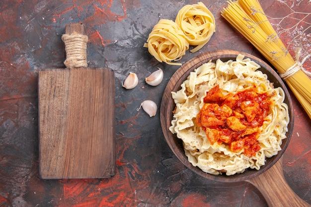 Pollo di vista superiore con il piatto di pasta della pasta sull'impasto scuro del piatto della pasta del pavimento scuro