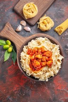 Pollo di vista superiore con il piatto di pasta della pasta sul piatto della pasta della pasta del pavimento scuro scuro