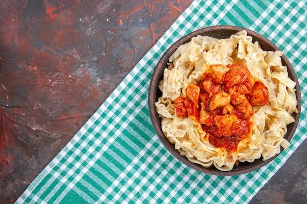 Pollo di vista superiore con il piatto di pasta della pasta sul piatto di pasta del pasto di colore di superficie scura