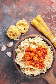 Pollo di vista superiore con il piatto di pasta della pasta sulla pasta scura del piatto di pasta di superficie scura