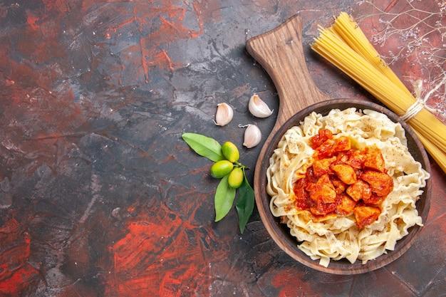 Vista dall'alto pollo con pasta piatto di pasta sulla superficie scura piatto pasta di pasta scura Foto Gratuite